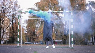 Beautiful hipster female dancing with a color smoke grenade near at gate
