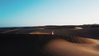 Beautiful horizontal landscape with desert, blue sky and the ocean behind. Woman in a dress is walking alone through the desert. Sunset light. Gran Canaria