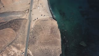 Beautiful landscape of turquoise ocean and sandy beach. Aerial footage over the beach with waves rolling in. Lonely road near the ocean. Gran Canaria