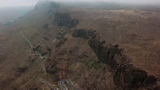 Bird eye view of camera flying between high rocks with the lonely winding road in the lowlands of the mountain. Beautiful landscape of foggy mountains. Aerial. Gran Canaria