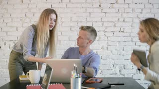 Business leader is sitting at the table and explaning something to employee on laptop. Coworkers team discussion business project using laptop