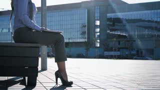 Business woman in high heel shoes on a sunny morning is sitting on a bench near the business center, opens a laptop and works