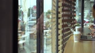 Business women meeting in Coffee Shop using notebook Shot Through Window
