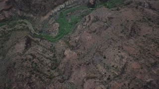 Camera flies over the mountain ridge with forest line meandering between rocks. Lonely road in the mountain cliff. Beautiful landscape with low hanging clouds. Aerial. Gran Canaria