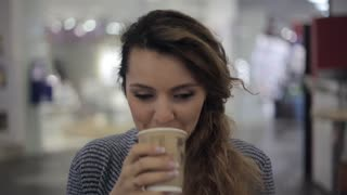 Cheerful girl having fun drinking coffe in cafe