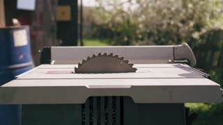 Circular saw starts to work. Slow motion rotating disk of industrial stationary circular saw.