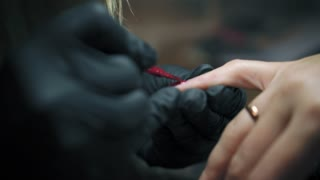 Close up shot of manicure master in black gloves is painting woman's little finger with red nail polish in nail salon. Female's hand with red nailpolish after the manicure