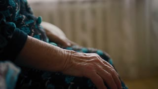Closeup view on eldery woman's wrinkled hands on knees
