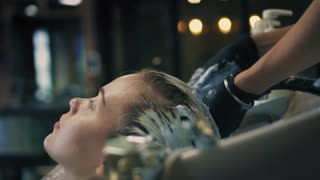 Closeup view on hairdresser in professional gloves is colouring woman's long blonde strands of hair in sink, while she is relaxing in hair salon. Slow mo.