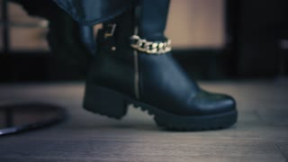 Closeup view on women's black winter boots with goldish chain in shoe store. Closeup.