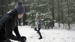 Couple man and girl playing snowball together and have fun. Slow mo