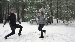 Couple playing snowballs. The girl throws a snowball and wins. Slow mo