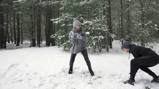Couple playing snowballs. The girl wins Slow mo