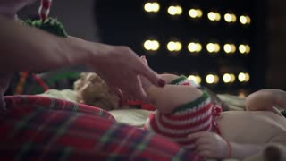Cute baby boy dressed in striped christmas clothes is lying on beige bed and smiling while mother carefully holding his feet