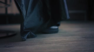 Cutted blonde woman's hair falling on the floor of the beauty salon. Closeup view. Slow mo