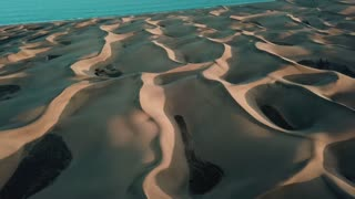 Desert landscape, wonderful sand dunes in sunset light. Aerial: horizon with an oringe desert and blue ocean. Gran Canaria