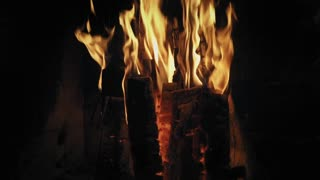 Down-up footage of real fireplace full of wood and fire. Detailed fire background. Slow mo.
