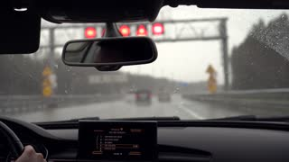 Driving car in the rain with the wipers on