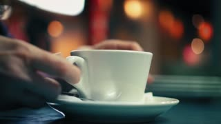 Elderly woman is gently taking cup with coffee, drinking it and take back on a plate in cafe. Closeup view