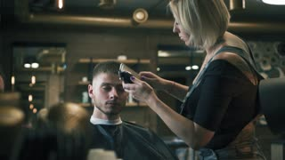 Female hairdresser is shaving man with electric razor in hair salon. Professional barber is cutting hair with hair trimmer. Hairstyling process
