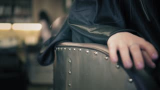 Female put a hand with beautiful ring on brown chair. Closeup view