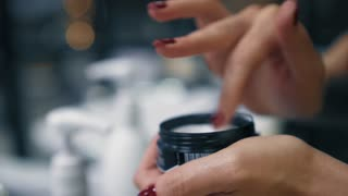Female softly takes beauty cream with fingers from black jar. Closeup