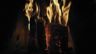 Fireplace burning closeup. Cozy warm burning fire in a brick fireplace. Cozy background. Slow mo