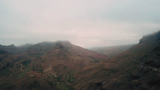 Flying over mountain cliffs. Majestic nature landscape with foggy mountain peaks and lonely roads. Aerial. Gran Canaria