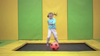 Girl jumping on a trampoline with a ball in a trampoline center