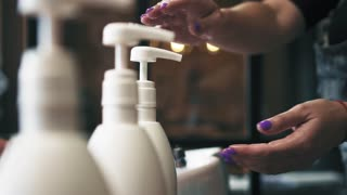 Hair dresser press the bottle with conditioner and squeezes it on her hand in hair saloon. Hair care procedure in barbershop. Slow motion.