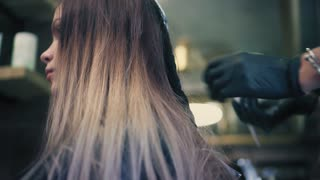 Hair stylist in black gloves is applying coloring dye on woman's hair to lighten up the hair tone in the beauty saloon.