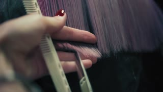 Hairdresser cuts the ends of long pink woman's hair in hair salon. Closeup, slow mo