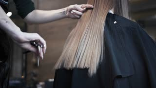 Hairdresser cuts the hair of a young girl with hair clippers and combs