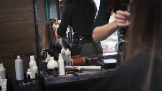 Hairdresser cuts the hair of a young girl with hair scissors and combs