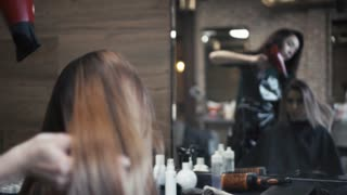 Hairdresser does a hairstyle for a woman with long hair with a hairdryer