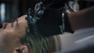 Hairdresser in black gloves carefully washes female's hair with conditioner in sink in hair salon, and then turns off the water. Closeup