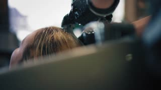 Hairdresser in black gloves washing blonde woman hair over sink in the beauty salon, closeup back view