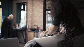 Hairdresser in gloves washes the brunette girl's hair in a stylish beauty salon. barbershop