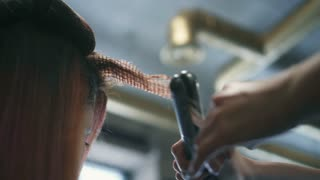 Hairdresser makes wavy hair with tongs. Hands close up view.
