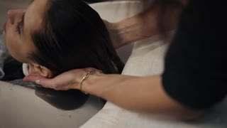 Hairdresser wipes the brunette girl's hair in a stylish beauty salon. barbershop