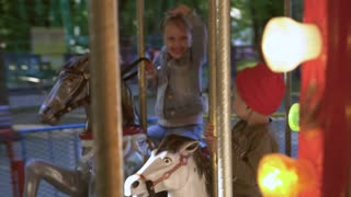 Happy children play together and ride a retro carousel with horses