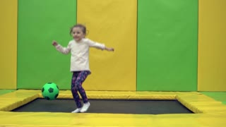Happy litle girl jumping on a trampoline with a ball. Slow Motion