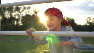 Happy little girl in a stylish baseball cap climbs up the stairs at sunset