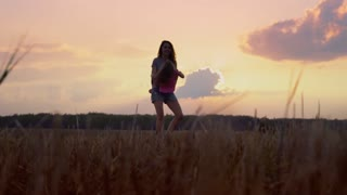 Happy mom and daughter spining round with long hair at sunset. Slow Mo