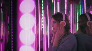 Happy woman is wearing headphones and dancing at party in pink neon lights. Hipster woman uses earphones. Slow mo