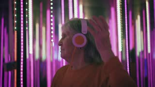 Hipster aged woman in headphones is dancing in colorful neon lights. Happy elderly female uses headphones and dancing in bright pink lights. Slow mo.