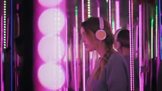 Hipster female in earphones leans to the mirror, looking in camera and smiling. Woman listen music in neon lights at party. Slow mo