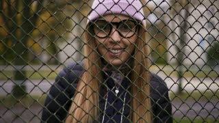 Hipster girl smiling near the fence and looking at the camera
