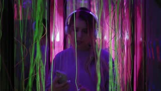 Hipster woman in headphones is taking selfie on smartphone, dancing in pink neon lights in the party and smiling. Beautiful woman listens music in earphones. Slow mo.