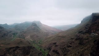 Horizontal view of gloomy mountain peaks hiding in clouds. Flying over mountains with lonely winding roads. Aerial. Gran Canaria